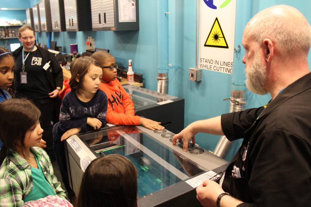 Seiji and other children learning about laser cutting at the Museum of Science and Industry's Fab Lab.